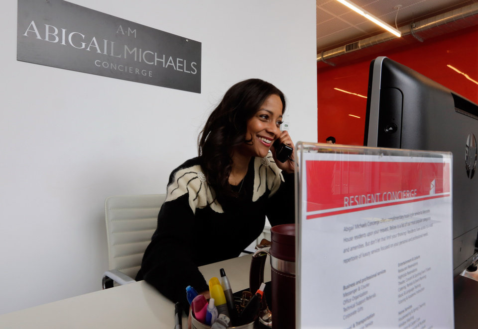 Photo - Zayna Abdul, 34, an Abigail Michaels concierge, works at her desk in the the Mercedes House apartments, in New York,  Monday, March 25, 2013. A brownstone overlooking Central Park is no longer enough for the well-to-do New Yorker on the hunt for an apartment. What the very wealthy want now is the ease of hotel living in their own apartment buildings. That means room service delivered from the restaurant down the street, a concierge who will handle even the most outlandish requests and, of course, a spa in the lobby. There is no amenity left behind in Manhattan's soaring luxury real estate market.(AP Photo/Richard Drew)