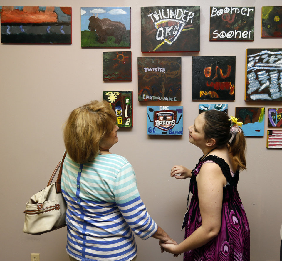 Photo - Allie Jelinek, right, shows Ginger Rader, a former counselor at the Youth and Family Services in Canadian County, some of the art she and others created at the Big Swanky Art Camp. It was on display Friday at the Big Swanky Art Show at Rainbow Fleet, 3024 Paseo .  Photos by Nate Billings, The Oklahoman  NATE BILLINGS -  NATE BILLINGS