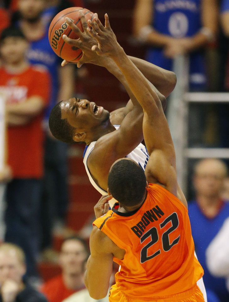 Photo - Kansas center Joel Embiid, back, is fouled by Oklahoma State guard Markel Brown (22) during the second half of an NCAA college basketball game at Allen Fieldhouse in Lawrence, Kan., Saturday, Jan. 18, 2014. Brown fouled out on the play. Kansas defeated Oklahoma State 80-78. (AP Photo/Orlin Wagner)