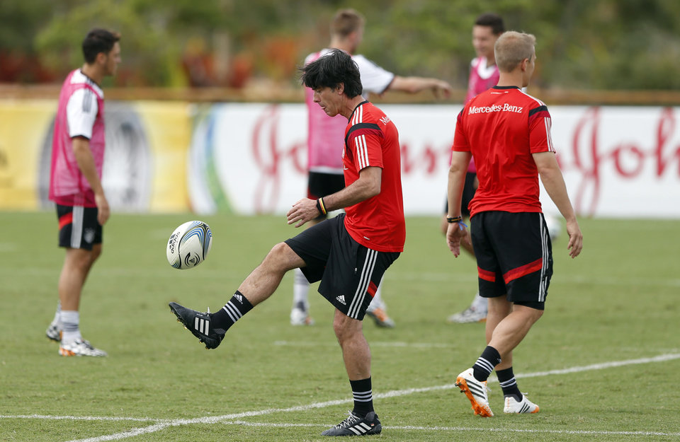 Photo - German national soccer team head coach Joachim Loew kicks a football during a training session in Santo Andre near Porto Seguro, Brazil, Monday, June 23, 2014. Germany play in group G of the 2014 soccer World Cup. (AP Photo/Matthias Schrader)