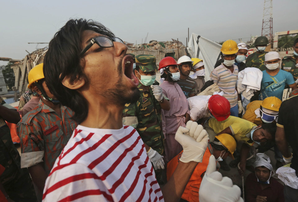 A Bangladeshi rescue worker shouts as others remove the body of a dead garment worker after it was retrieved from a building that collapsed on Wednesday in Savar, near Dhaka, Bangladesh, Sunday, April 28, 2013. Bangladesh rescuers on Sunday located nine people alive inside the rubble of the multi-story building, as authorities announced they will now use heavy equipment to drill a central hole from the top to look for survivors and dead bodies. (AP Photo/Kevin Frayer)