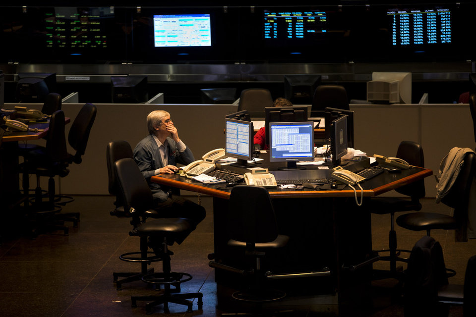 Photo - FILE - In this Tuesday, Oct. 23, 2012, file photo,  abroker works at the Buenos Aires Stock Exchange in Buenos Aires, Argentina.  From Turkey to South Africa to Argentina, emerging markets are being slammed by rising inflation, economic mismanagement and political turmoil. (AP Photo/Victor R. Caivano)