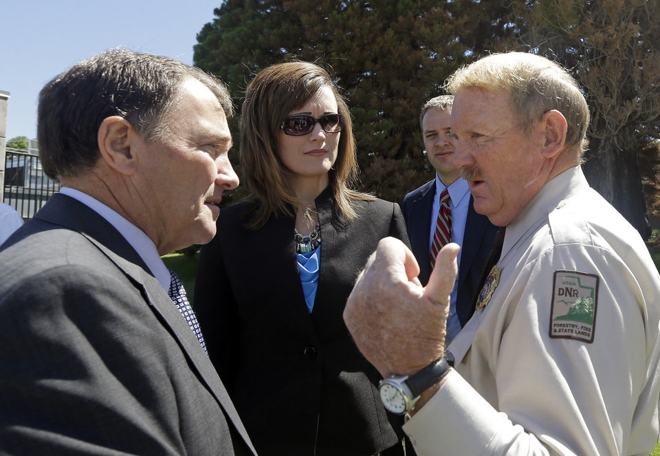 Photo - Utah Gov. Gary Herbert, left,  speaks with State Forester Dick Buehler, right, after a news conference Friday, June 14, 2013, at the Utah State Capitol, in Salt Lake City. Herbert is sending the Utah National Guard to help fight raging wildfires in Colorado Springs. The state will send two helicopters and several crews starting Saturday. Two people have been killed and 379 homes destroyed in the Colorado Springs wildfire. He also urged Utah residents to use caution as Utah enters its fire season.  (AP Photo/Rick Bowmer)