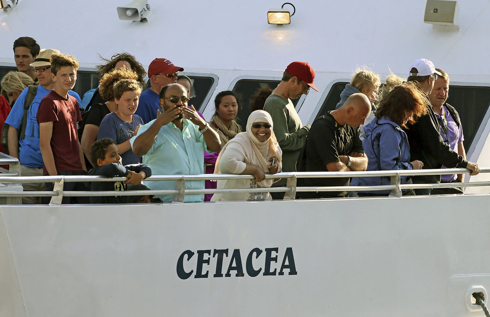 Photo - Passengers stand on deck of the whale watch boat Cetacea as it docks Tuesday morning, July 29, 2014 at Long Wharf in Boston. The boat snagged a lobster trap rope during a whale watching excursion about 15 miles off the coast of Massachusetts late Monday, and had to spend a night at sea before divers freed it Tuesday morning. Two Coast Guard cutters remained with the vessel during the night. No injuries were reported to any of the 157 passengers or six crew members. (AP Photo/Boston Herald, Mark Garfinkel)
