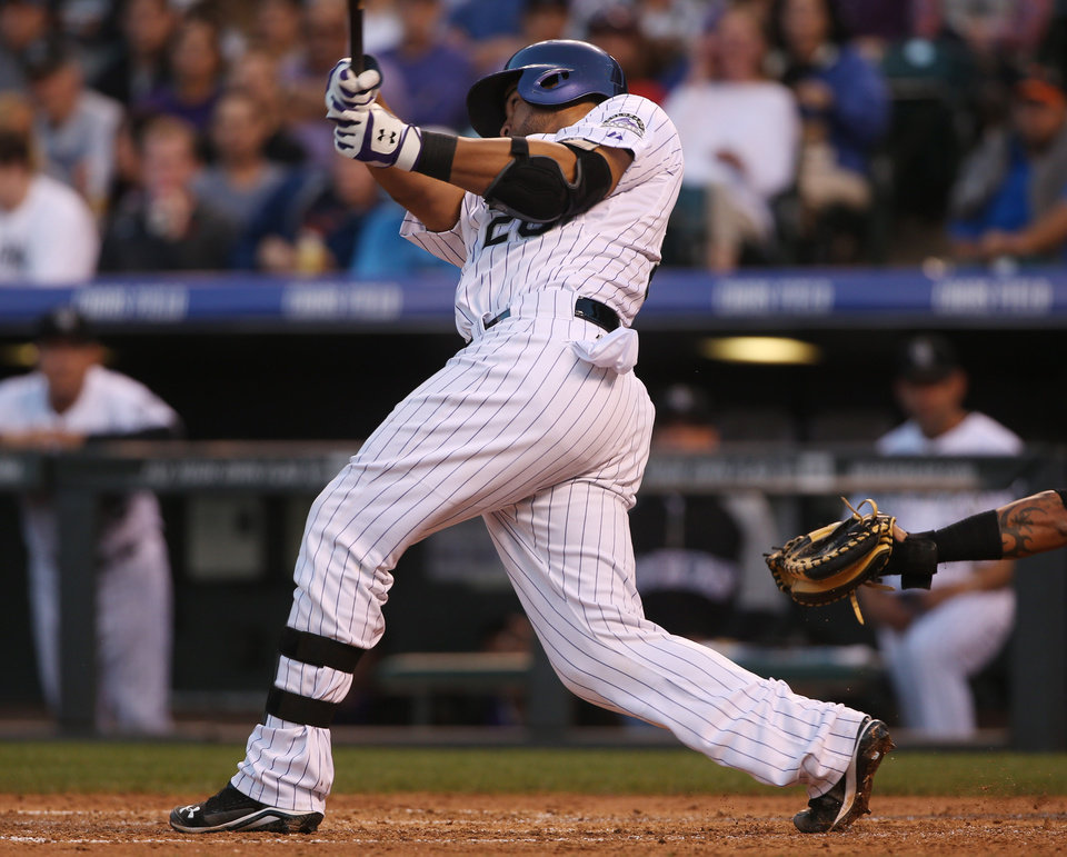 Photo - Colorado Rockies' Wilin Rosario follows the flight of his RBI-double against the San Francisco Giants in the fourth inning of a baseball game in Denver on Tuesday, May 20, 2014. (AP Photo/David Zalubowski)