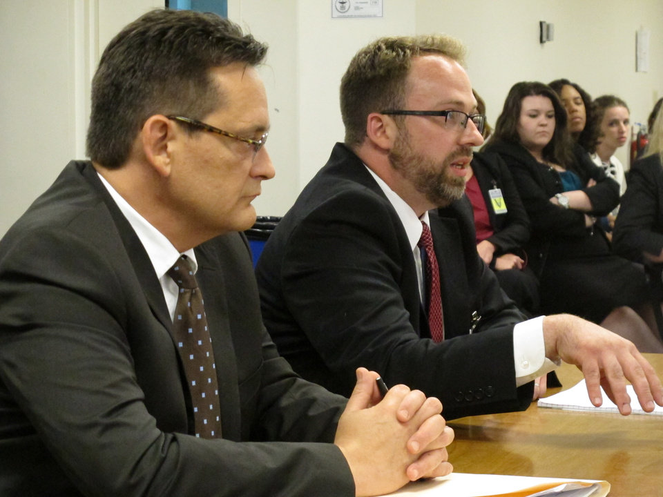 In this photo taken Monday, July 8, 2013, Assistant Cuyahoga County Prosecutor Matthew Meyer, right, explains to the Ohio Parole Board why his office is recommending that condemned killer Billy Slagle\'s death sentence be commuted to life without parole, as fellow Cuyahoga County prosecutor Allan Regas listens, in Columbus, Ohio. Meyer\'s boss, Cuyahoga County Prosecutor Tim McGinty, wants capital punishment cases to be the exception in his office, not the rule. (AP Photo/Andrew Welsh-Huggins)