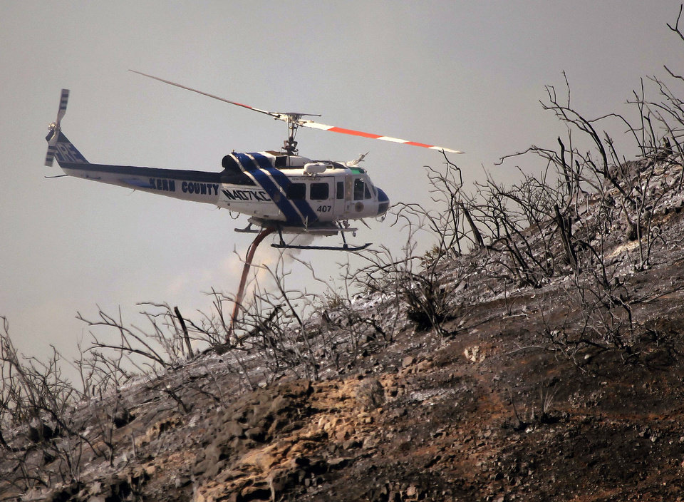 Photo - A Kern County Fire helicopter makes a water drop on a hotspot over a hill near Thousand Oaks, Calif. on Thursday, May 2, 2013. Authorities have ordered evacuations of a neighborhood and a university about 50 miles west of Los Angeles where a wildfire is raging close to subdivisions. The blaze on the fringes of Camarillo and Thousand Oaks broke out Thursday morning and was quickly spread by gusty Santa Ana winds. Evacuation orders include California State University, Channel Islands. (AP Photo/Nick Ut)