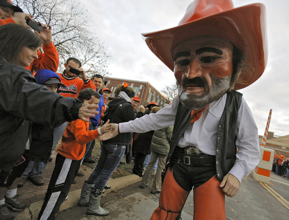 Photo - Pistol Pete interacts with the Oklahoma State fans while in the 'Spirit Walk' before the Bedlam college football game between the Oklahoma State University Cowboys (OSU) and the University of Oklahoma Sooners (OU) at Boone Pickens Stadium in Stillwater, Okla., Saturday, Dec. 3, 2011. Photo by Chris Landsberger, The Oklahoman