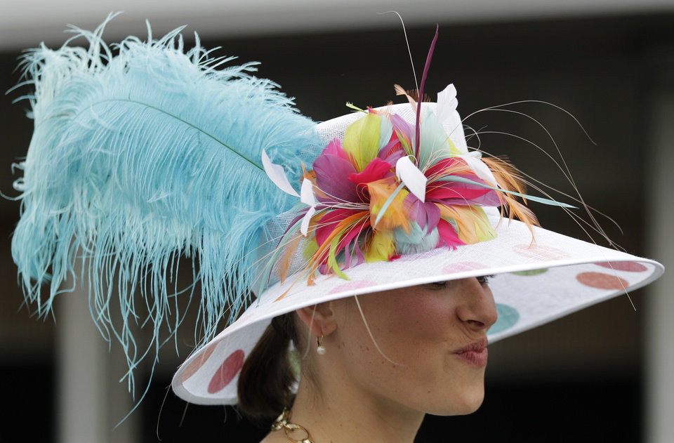 A spectator wears a fancy hat through the paddock area before the 138th Kentucky Derby horse race at Churchill Downs Saturday, May 5, 2012, in Louisville, Ky. (AP Photo/Mark Humphrey)  ORG XMIT: DBY127