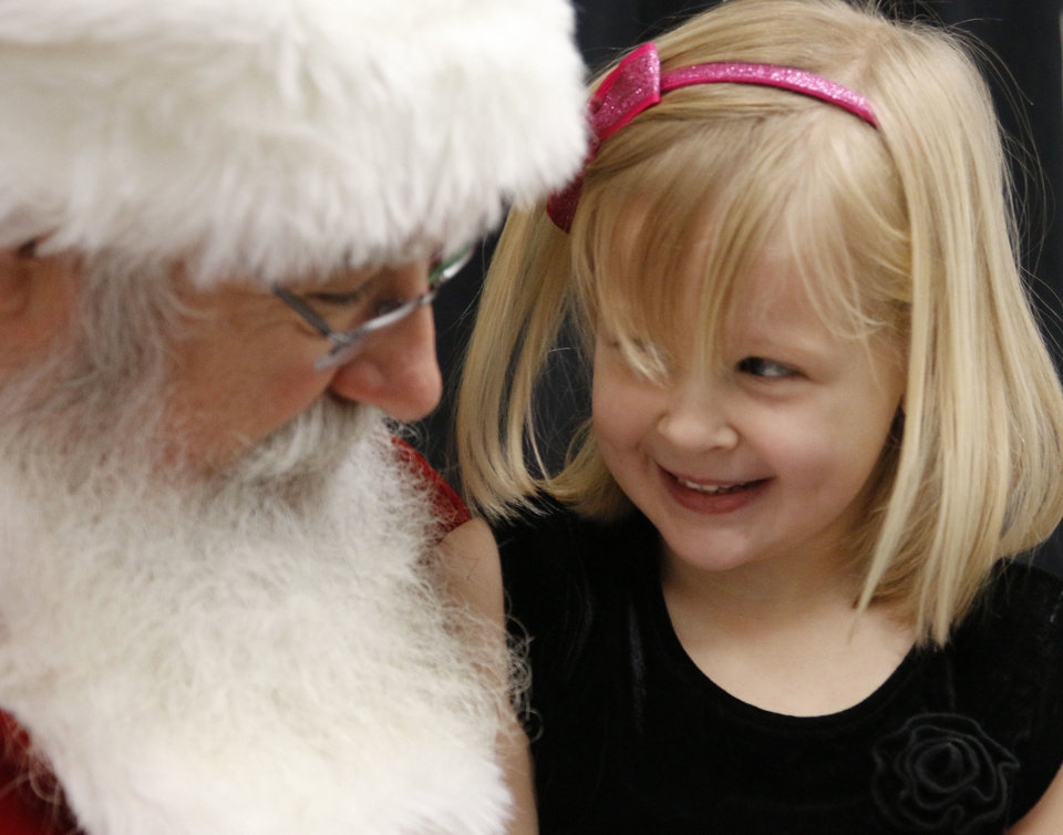 Photo - Santa brings a smile to Kylie Rowe, 4, during their visit at an  Edmond Police Department event.  Photo by Paul Hellstern, The Oklahoman  PAUL HELLSTERN - Oklahoman