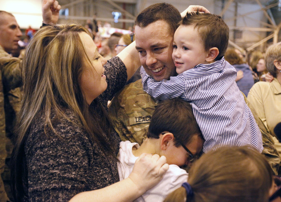 Sgt. Thomas Leach gets hugs from his wife Holly and boys Tommy, 10, and Noah, 2, as soldiers from the 45th return from a year's deployment in Afghanistan to waiting family members in Oklahoma City, OK, Saturday, March 3, 2012. By Paul Hellstern, The Oklahoman