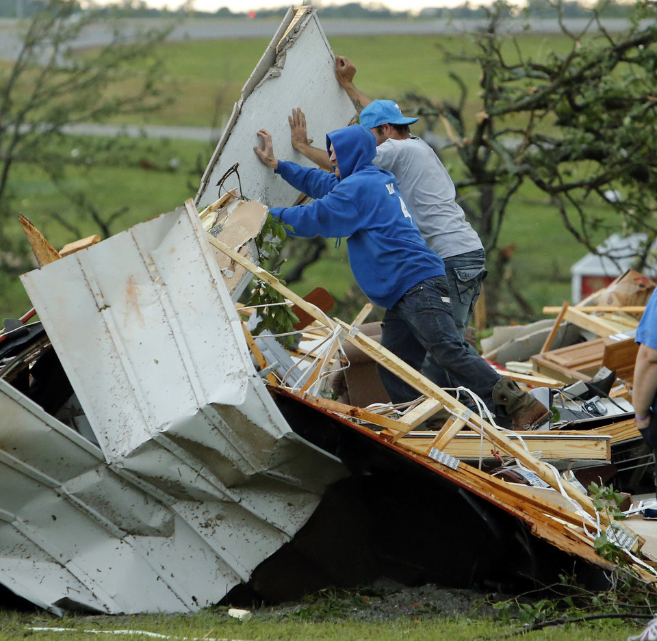 Photo - Jeff Stark gets help uncovering valuables from friend Frankie Lovejoy after a tornado ripped through Bridge Creek, Okla. on Wednesday, May 6, 2015.  Photo by Steve Sisney, The Oklahoman