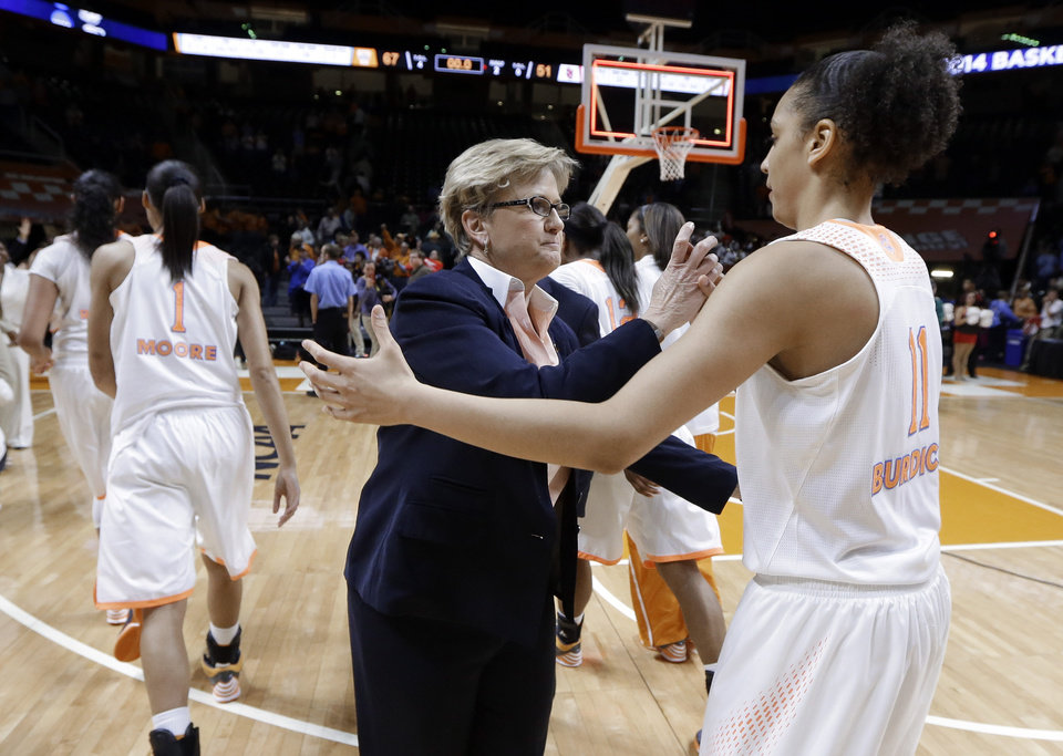 Photo - Tennessee head coach Holly Warlick, center, congratulates Cierra Burdick (11) after an NCAA women's college basketball second-round tournament game against St. John's Monday, March 24, 2014, in Knoxville, Tenn. Burdick led Tennessee with 21 points as they won 67-51. (AP Photo/Mark Humphrey)