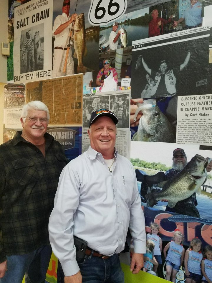 Photo -  Chris Lindenberg, right, owner of Gene Larew Lures and Bobby Garland Crappie Baits, is standing with George Toalson, product designer and plant manager, in front of a wall mural at the company's Tulsa headquarters. [PHOTO BY ED GODFREY, THE OKLAHOMAN]