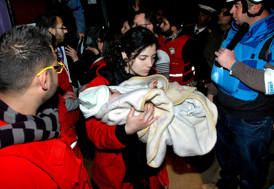 Photo - In this photo taken on Monday Feb. 10, 2014, and released by the Syrian official news agency SANA, a Syrian Arab Red Crescent member in red uniform carries a baby on to a bus to evacuate the battleground city of Homs, Syria. The Syrian government has allowed 111 men of fighting age to leave rebel-held areas of the besieged city of Homs after they were questioned and cleared of rebel links. (AP Photo/SANA)