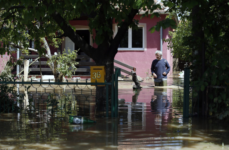 Photo - A man walks in front of a his flooded home in the village of Veliki Crljeni, some 30 kilometers (18 miles) south of Belgrade, Serbia, Sunday, May 18, 2014. In Serbia, more than 20,000 people have been forced from their homes. Officials there fear more flooding later Sunday as floodwaters travel down the Sava and reach the country. Serbian officials said that the flood wave might be lower than initially expected, because the river broke barriers upstream in Croatia and Bosnia. Experts said they expect Sava floodwaters to rise for two more days, then subside. (AP Photo/Darko Vojinovic)