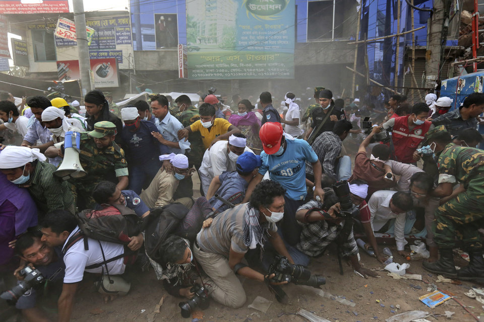 Photo - Bangladeshi rescue workers and media fall on top of each other in a stampede after the crowd panic when someone shouted a section of building might collapse, at the site of a building that collapsed Wednesday in Savar, near Dhaka, Bangladesh, Friday, April 26, 2013. The death toll reached hundreds of people as rescuers continued to search for injured and missing, after a huge section of an eight-story building that housed several garment factories splintered into a pile of concrete.(AP Photo/Kevin Frayer)