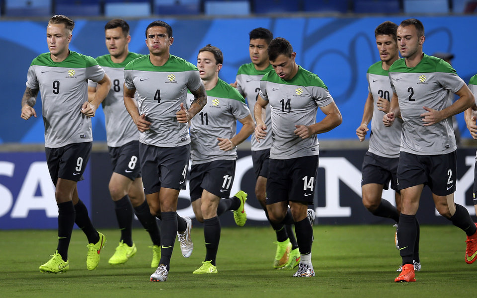 Photo - Australia's Tim Cahill, third left, and his teammates jog during a training session the day before the group B World Cup soccer match between Chile and Australia in the Arena Pantanal in Cuiaba, Brazil, Thursday, June 12, 2014. (AP Photo/Michael Sohn)