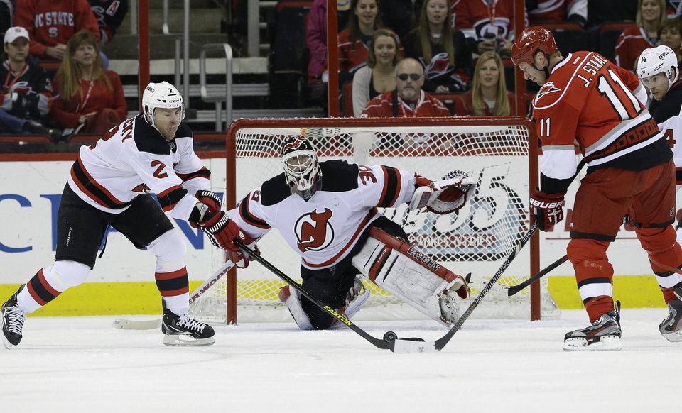 New Jersey Devils goalie Martin Brodeur (30) and teammate Marek Zidlicky (2), of the Czech Republic, defend the goal against Carolina Hurricanes' Jordan Staal (11) during the first period of an NHL hockey game in Raleigh, N.C., Thursday, March 21, 2013. (AP Photo/Gerry Broome)