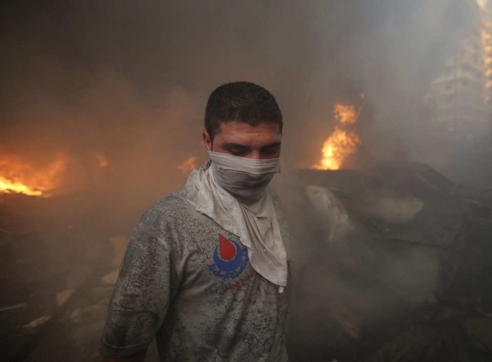 Photo - A Hezbollah civil defense worker walks past a burned car at the site of a car bomb explosion in southern Beirut, Lebanon, Thursday, Aug. 15, 2013. The powerful car bomb ripped through a southern Beirut neighborhood that is a stronghold of the militant group Hezbollah on Thursday, killing people and trapping others in burning buildings, the media said. (AP Photo/Hussein Malla)