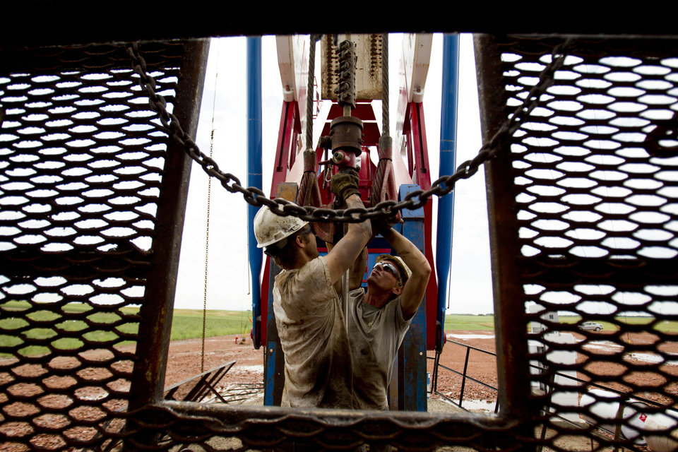 Photo - FILE - In this July 26, 2011 file photo, Austin Mitchell, left, and Ryan Lehto work on an oil derrick outside of Williston, N.D. In 2012, domestic crude oil production achieved its biggest one-year gain since 1951, driven by output in North Dakota and Texas. The United States is on pace to pass Saudi Arabia as the world's top oil producer within two years. (AP Photo/Gregory Bull, File)