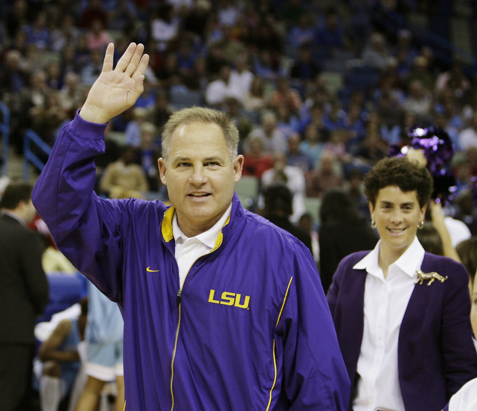 Photo - Louisiana State University (LSU) college football coach Les Miles, with his wife Kathy Miles waves at the fans during the LSU-Louisiana Tech women's college basketball game in New Orleans, Saturday, Dec. 30, 2006. LSU plays Notre Dame in the Sugar Bowl on Jan. 3, 2007.(AP Photo/Alex Brandon) ORG XMIT: LAAB109