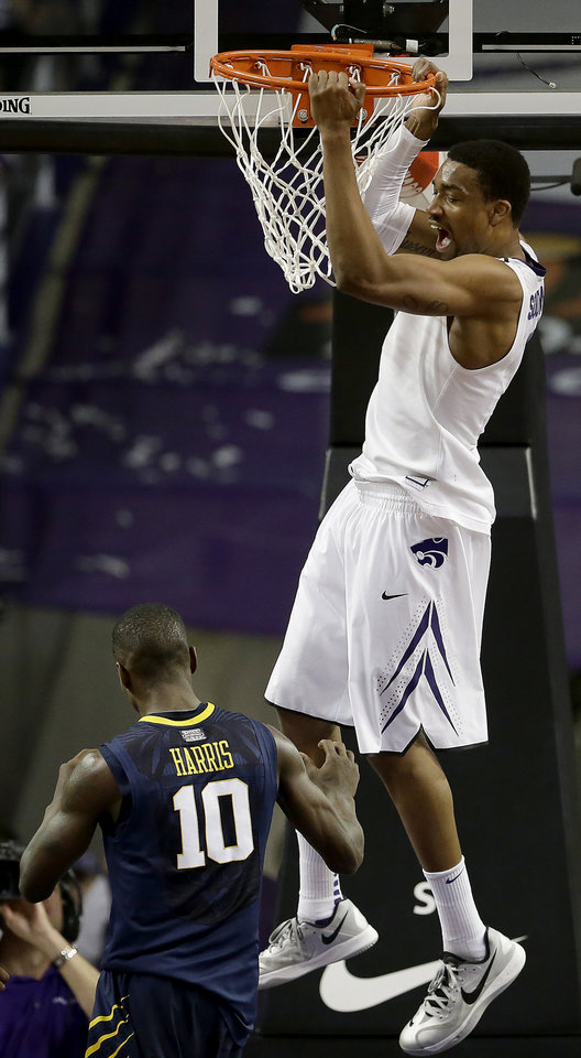 Photo - Kansas State's Shane Southwell gets past West Virginia's Eron Harris to dunk the ball during the first half of an NCAA college basketball game Saturday, Jan. 18, 2014, in Manhattan, Kan. (AP Photo/Charlie Riedel)