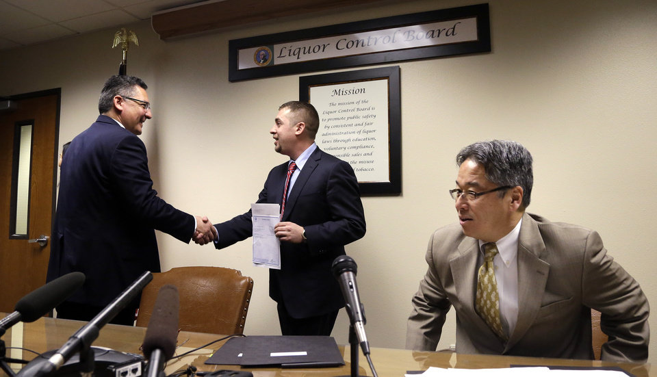 Photo - Sean Green, center, is congratulated by Washington State Liquor Control Board Director Rick Garza, left, as board member Chris Marr returns to his seat after Green received his new legal marijuana license Wednesday, March 5, 2014, in Olympia, Wash. Green, a medical marijuana dispensary operator from Spokane, was issued the producer-processor license under the state's recreational pot law at the Liquor Control Board meeting. (AP Photo/Elaine Thompson)