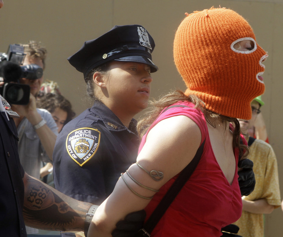 Photo -   A protester is arrested during a demonstration in front of the Russian consulate in support of Russian punk band Pussy Riot, Friday, Aug. 17, 2012 in New York. A Russian judge found three members of the provocative punk band guilty of hooliganism on Friday, in one of the most closely watched cases in recent Russian history. The judge said the three band members committed hooliganism driven by religious hatred and offending religious believers. The three were arrested in March after a guerrilla performance in Moscow's main cathedral calling for the Virgin Mary to protect Russia against Vladimir Putin, who was elected to a new term as Russia's president a few days later.(AP Photo/Alex Katz)