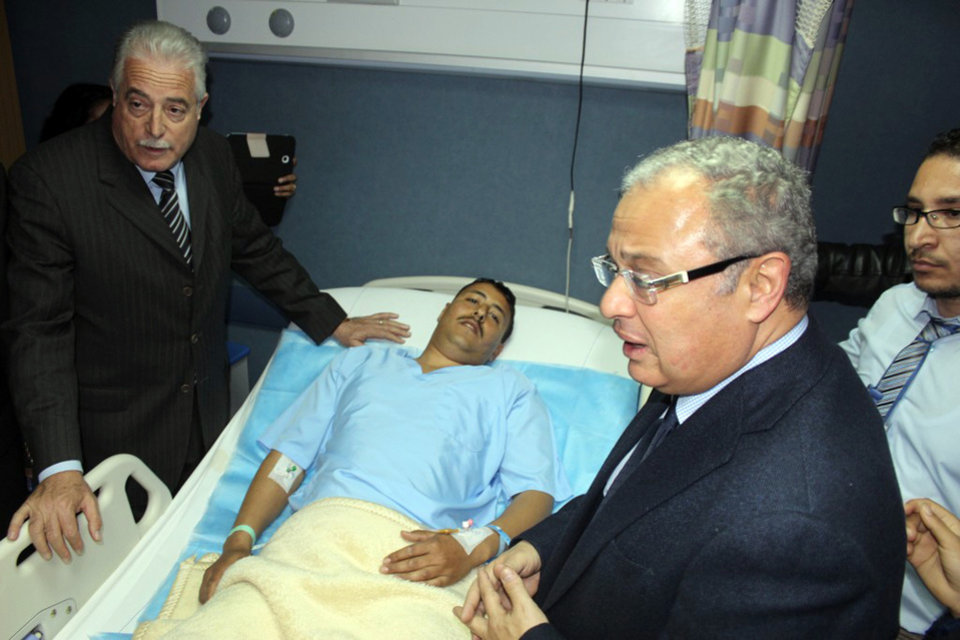 Photo - In this Sunday, Feb. 16, 2014 photo released by the Office of the South Sinai Governor, shows the Governor of South Sinai, Major General Khaled Foda, left, and Egyptian Minister of Tourism Hesham Zazou, second right, visit an unidentified Egyptian who was wounded in an explosion as a bus attempted to travel into Israel from Egypt near the Taba border crossing on Sunday, at a hospital in Sharm el-Sheik, South Sinai, Egypt. An explosion tore through a bus filled with South Korean sightseers in the Sinai Peninsula on Sunday, killing at least four people and raising fears that Islamic militants have renewed a bloody campaign to wreck Egypt's tourism industry. The bombing near the tip of the Red Sea's Gulf of Aqaba was the first attack against tourists in Sinai in nearly a decade. (AP Photo/Office of the South Sinai Governor )
