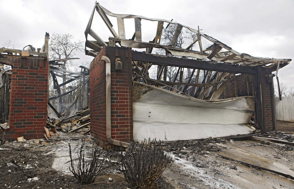 Photo - The remains from a house that was destroyed by wildfires on Friday, April 10, 2009, in Midwest City, Okla.  Photo by Chris Landsberger, The Oklahoman