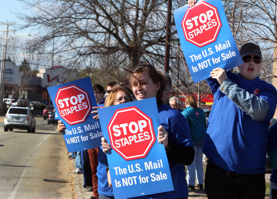 Photo - Postal workers picket in front of a Staples store Thursday, April 24, 2014, in Concord, N.H.  Postal workers around the country protested in front of Staples stores, objecting to the U.S. Postal Service's pilot program to open counters in stores, staffed with retail employees. (AP Photo/Jim Cole)