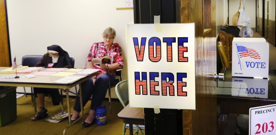 Photo - Precinct 203 poll workers read books to fill time between voters in the early afternoon at Trinity Baptist Church, on NW 23 just west of Classen Blvd., on Tuesday, June 28, 2016. Photo by Jim Beckel, The Oklahoman