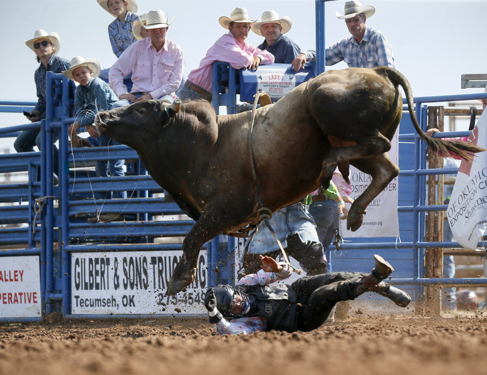 Photo - Ryan Albers of Okeechobee, Florida, tries to get out of the way of a bull after being thrown while competing in bull riding during the International Finals Youth Rodeo at the Heart of Oklahoma Exposition Center in Shawnee, Okla., Thursday morning, July 11, 2019. [Nate Billings/The Oklahoman]