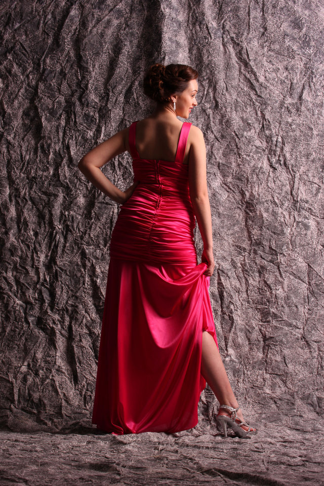 Model Keely wears a Neon pink satin gown with ruched bodice and jeweled detailing at the V-neck , $92.50. Silver metallic jewel-encrusted sandal $40.50. All sold at Deb Shops. Photo by Steve Webb, for The Oklahoman. <strong></strong>