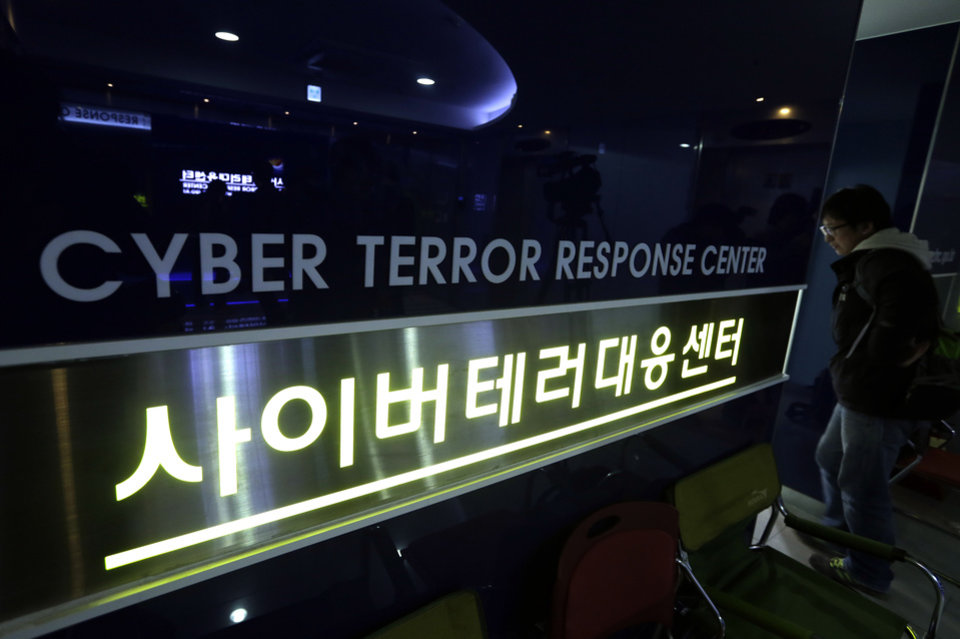 Photo - A man walks past next to a sign of Cyber Terror Response Center at National Police Agency in Seoul, South Korea, Thursday, March 21, 2013. A Chinese Internet address was the source of a cyberattack on one company hit in a massive network shutdown that affected 32,000 computers at six banks and media companies in South Korea, initial findings indicated Thursday. (AP Photo/Lee Jin-man)