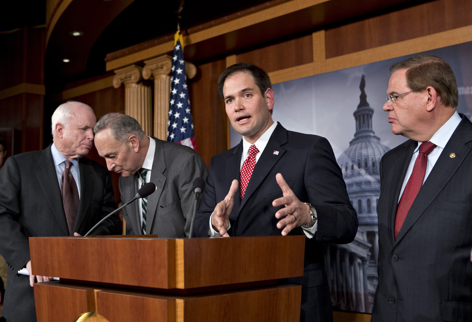 Sen. Marco Rubio, R-Fla.. center, answers a reporter's question as he and a bipartisan group of leading senators announce that they have reached agreement on the principles of sweeping legislation to rewrite the nation's immigration laws, during a news conference at the Capitol in Washington, Monday, Jan. 28, 2013. From left are Sen. John McCain, R-Ariz., Sen. Charles Schumer, D-N.Y., Sen. Marco Rubio, R-Fla., and Sen. Robert Menendez, D-N.J. The deal covers border security, guest workers and employer verification, as well as a path to citizenship for the 11 million illegal immigrants already in this country.  (AP Photo/J. Scott Applewhite)