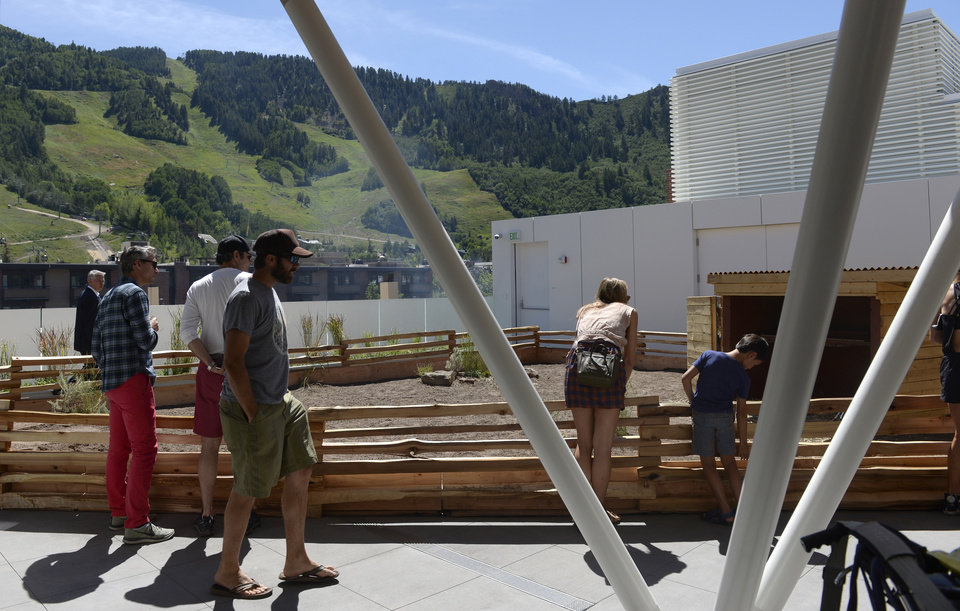 Photo - This Aug. 2, 2014 photo shows people at an opening at the Aspen Art Museum in Aspen, Colo. A group of protesters are objecting to Aspen Art Museum officials who plan to place iPads on tortoises during an art exhibition this weekend. The stunt is planned as a part of the 24-hour public opening of the new art museum on Saturday. The debut show on the rooftop sculpture garden, put together by artist Cai Guo-Qiang, features tortoises wandering around the space with iPads attached to their shells with specially designed mounts. The iPads will be showing footage of abandoned ghost-town cabins from around the valley, images that were previously recorded with the devices while they were attached to the tortoises' shells. (AP Photo/The Denver Post, Kathryn Scott Osler)