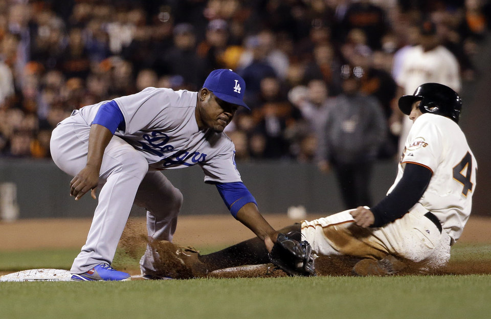 Photo - San Francisco Giants' Hunter Pence, right, is safe at third base past the tag attempt from Los Angeles Dodgers third baseman Juan Uribe after a wild pitch during the sixth inning of a baseball game on Tuesday, April 15, 2014, in San Francisco. (AP Photo/Marcio Jose Sanchez)