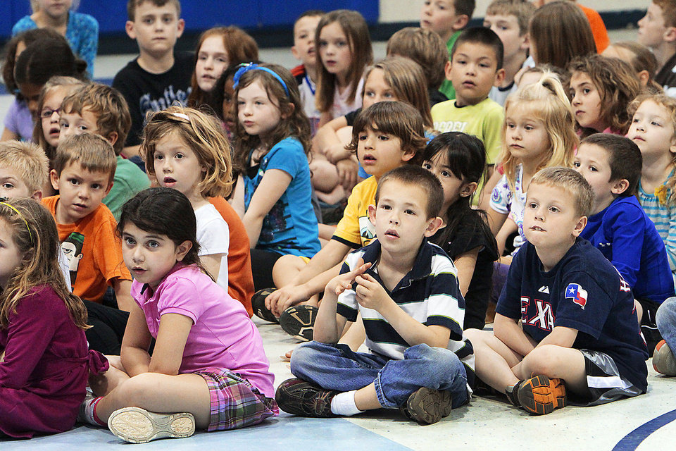 Photo - Students watch the members of the Oklahoma Veterans Flag Program demonstrate the proper way to fold an American flag at Prairie Vale Elementary School in Oklahoma City on Thursday. Photos By David McDaniel, The Oklahoman
