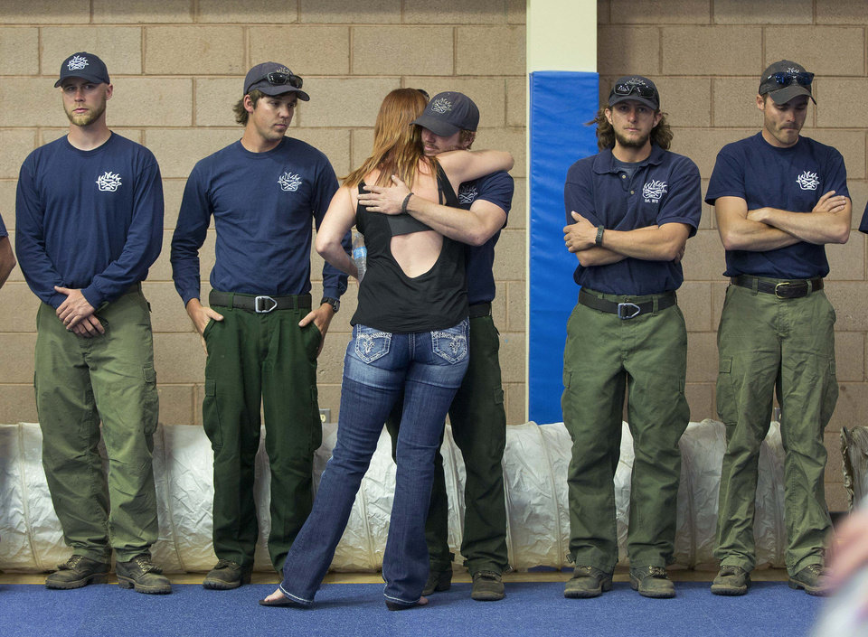 Photo - A woman hugs a firefighter before the start of a memorial service, Monday, July 1, 2013 in Prescott, Ariz. The service was held for the 19 Granite Mountain Hotshot Crew firefighters who were killed Sunday, when an out-of-control blaze overtook the elite group. (AP Photo/Julie Jacobson)