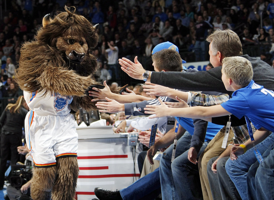 Photo - Oklahoma City mascot Rumble the Bison slaps the hands of Thunder fans during the NBA basketball game between the Orlando Magic and Oklahoma City Thunder in Oklahoma City, Thursday, January 13, 2011. Oklahoma City won, 125-124. Photo by Nate Billings, The Oklahoman