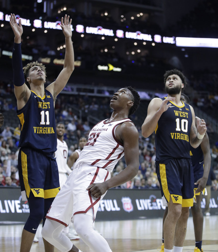 Photo - Oklahoma's Kristian Doolittle (21) watches with West Virginia's Emmitt Matthews Jr. (11) and Jermaine Haley (10) as Doolittle's shot slowly falls through the rim during the second half of an NCAA college basketball game in the Big 12 men's tournament Wednesday, March 13, 2019, in Kansas City, Mo. West Virginia won 72-71. (AP Photo/Charlie Riedel)