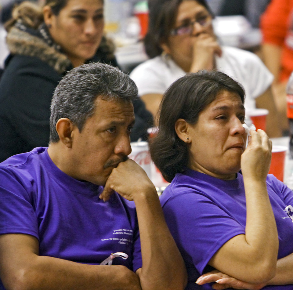 Photo - Elvira Gonzalez wipes a tear from her eye as she and her husband Hector watch members of the Yumare Mexican Folkloric Dancers perform during a benefit dinner for the family of homicide victim Jasmen Gonzalez at John Glenn Elementary on Wednesday, Nov. 16, 2011. in Oklahoma City, Okla. Jasmen was a member of the dance troop that performed in her honor. Photo by Chris Landsberger, The Oklahoman  ORG XMIT: KOD