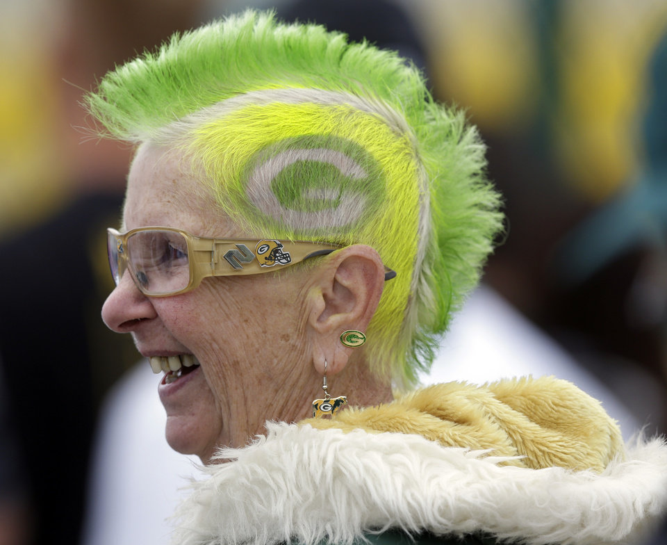 Green Bay Packers fan Mary Steinkraus of Germantown, Wis., watches the team practice during NFL football training camp Saturday, July 27, 2013, in Green Bay, Wis. (AP Photo/Morry Gash)