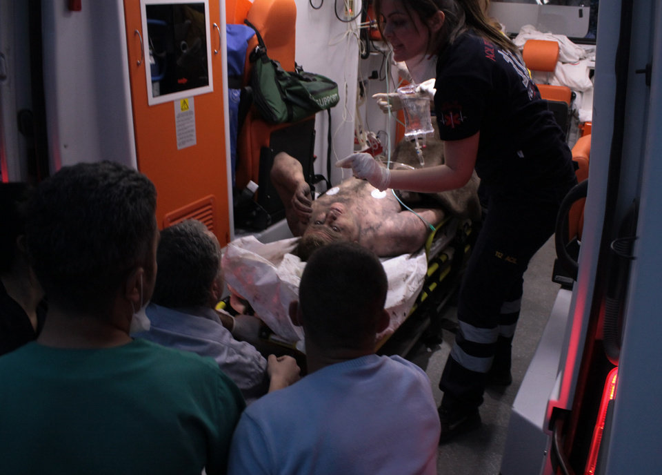 Photo - Medics place an injured miner into an ambulance after an explosion and fire at a coal mine in Soma, in western Turkey, Tuesday, May 13, 2014.  An explosion and fire at a coal mine in western Turkey killed at least one miner Tuesday and left up to 300 workers trapped underground, a Turkish official said. Twenty people were rescued from the mine in the town of Soma in Manisa province but one later died in the hospital, Soma administrator Mehmet Bahattin Atci told reporters. The town is 250 kilometers (155 miles) south of Istanbul. (AP Photo/Depo Photos)