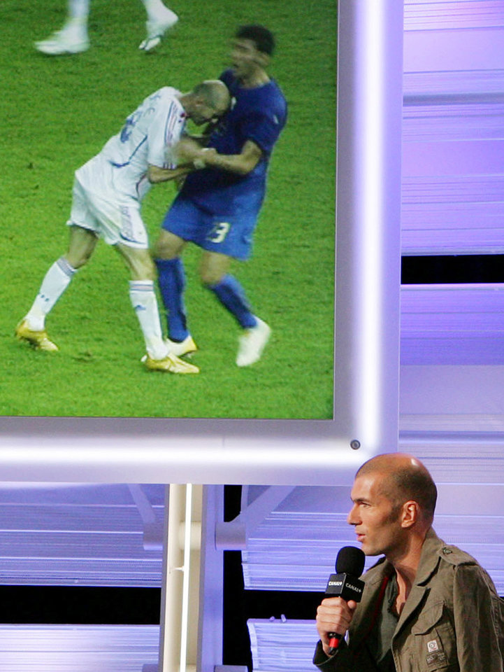 FILE - In this July 12, 2006 photo released by Canal Plus, French soccer star Zinedine Zidane talks during a television interview, in Paris, while a photo in the background shows Zidane giving Italy's Marco Materazzi a head-butt during a World Cup soccer match. Violence is part of the game in many sports. But when athletes cross the line it can attract the attention of authorities _ sometimes from within their sport and in other cases from criminal prosecutors. The punishment of four members of the New Orleans Saints for participating a cash-for-hits bounty system targeting opponents is the latest example but not the only one. (AP Photo/Daniel Bardou,Canal Plus) NO SALES