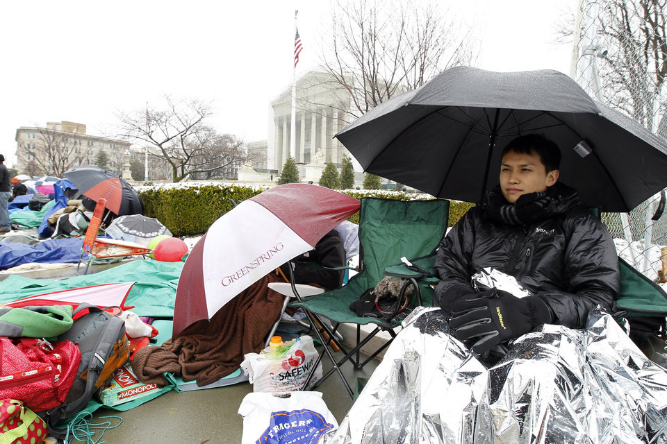 Photo - Wally Suphap from Calif., waits in line to enter Supreme Court in Washington, Monday March, 25, 2013, a day before the court will hear a same-sex marriage case. (AP Photo/Jose Luis Magana)