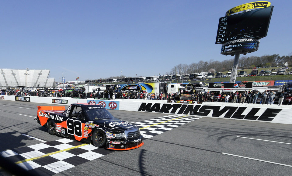 Driver Johnny Sauter (98) crosses the finish line to win the Kroger 250 NASCAR Truck series auto race at Martinsville Speedway in Martinsville, Va., Saturday, April 6, 2013.  (AP Photo/Steve Helber)