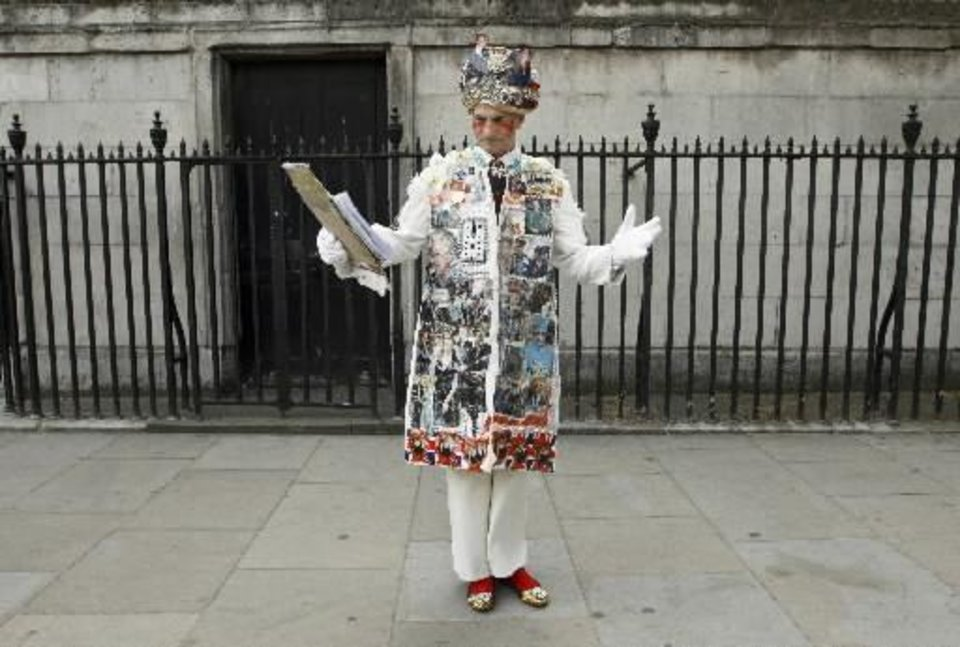 Photo - A royal enthusiast dressed with pictures of the royal family performs in the street in London, Thursday, April 28, 2011. Prince William and Kate Middleton are due to get married on Friday, April 29. (AP Photo/Daniel Ochoa de Olza)